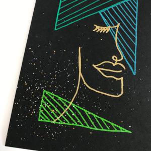 Schwarze Karte mit grünen Dreiecken und einem goldenen One-Line-Art Gesicht gestaltet mit dem Marabu Yono Marker