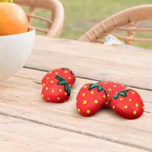 Kleine Steine bemalt mit dem Marabu Yono Marker wie Erdbeeren als Deko auf einem Tisch