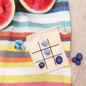 Kleine Steine bemalt mit dem Marabu Yono Marker als Tic-Tac-Toe Spielsteine auf einem Spielfeld im Sand